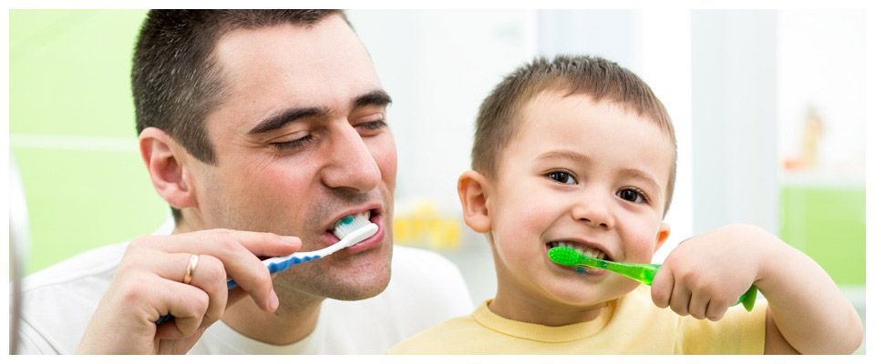 father and son brushing teeth